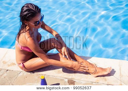 Portrait of a young woman sitting near swim pool and applying sun cream outdoors