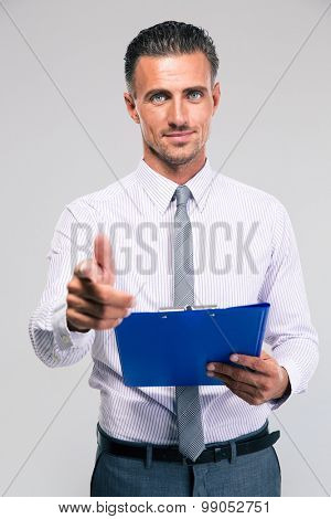 Happy businessman holding clipboard and showing gun gesture with fingers isolated on a white background. Looking at camera