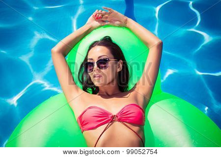 Portrait of attractive woman resting on air mattress in swimming pool