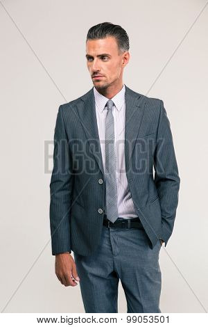 Portrait of a confident businessman standing isolated on a white background and looking away