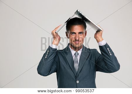 handsome businessman holding his laptop on his head like roof of house isolated on a white background. Looking at camera