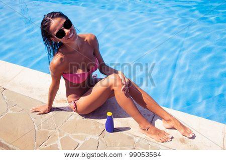 Portrait of a happy woman sunbathing near swim pool outdoors