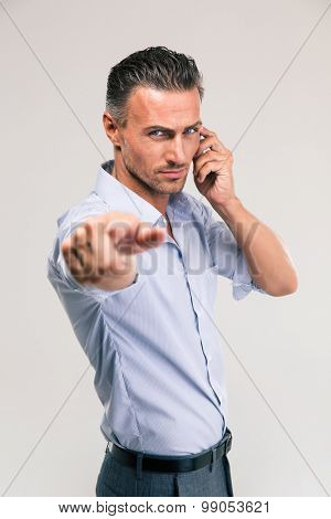 Serious businessman talking on the phone and pointing at camera isolated on a white background