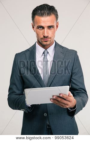 Portrait of a handsome businessman in suit using tablet computer and looking at camera over gray background