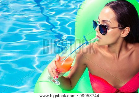 Portrait of a beautiful woman drinking cocktail while sitting on air mattress in swimming pool