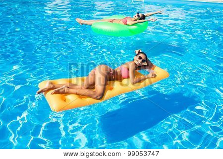 Portrait of a two women lying on air mattress in the swimming pool