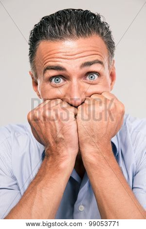 Portrait of a frightened man looking at camera isolated on a white background