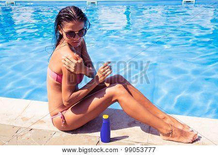 Portrait of a pretty woman sitting near swim pool and applying sun cream outdoors