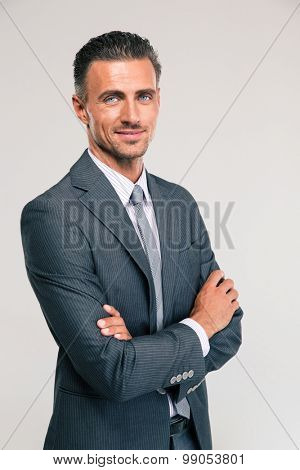 Portrait of a happy businessman standing with arms folded isolated on a white background