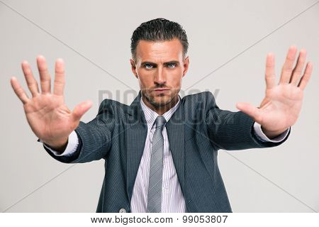 Portrait of a confident businessman showing stop gesture with palms isolated on a white background
