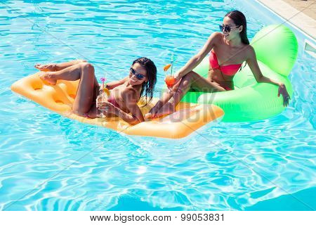 Smiling two girls resting on air mattress in swimming pool