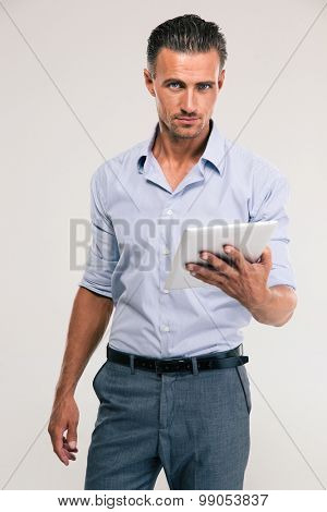 Portrait of a happy businessman holding tablet computer and looking at camera isolated on a white background