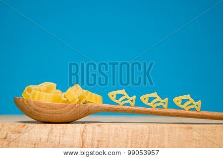 Pasta In The Form Of Animals And A Spoon On A Blue Background