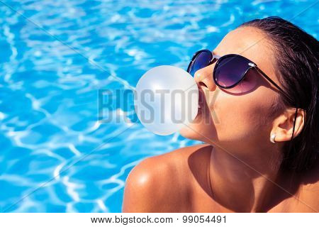 Charming woman in sunglasses blowing bubble with gum in swim pool outdoors