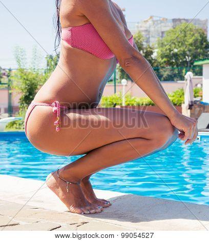 Closeup portrait of a woman squatting near swim pool outdoors