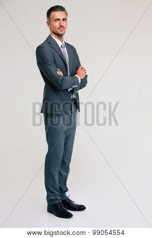 Full length portrait of a confident businessman standing with arms folded isolated on a white background. looking at camera