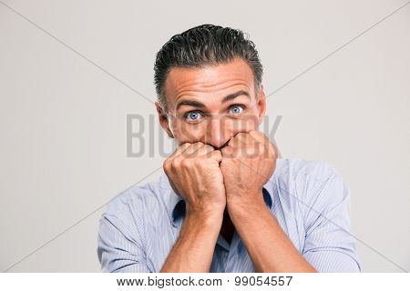 Portrait of a scared young man standing isolated on a white background