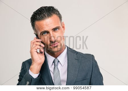 Portrait of a serious businessman talking on the phone isolated on a white background. Looking at camera