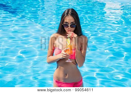 Portrait of a charming woman in sunglasses drinking cocktail in swimming pool