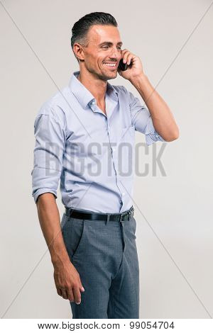 Portrait of a smiling handsome man talking on the phone and looking away isolated on a white background