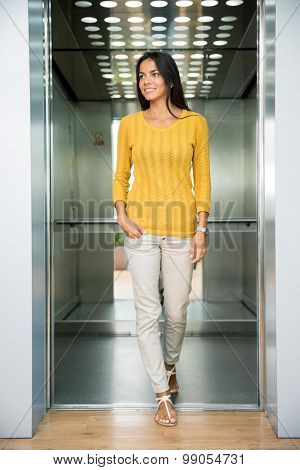 Portrait of a smiling casual businesswoman standing in elevator and looking away
