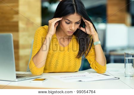 Portrait of a young casual businesswoman reading documents in office