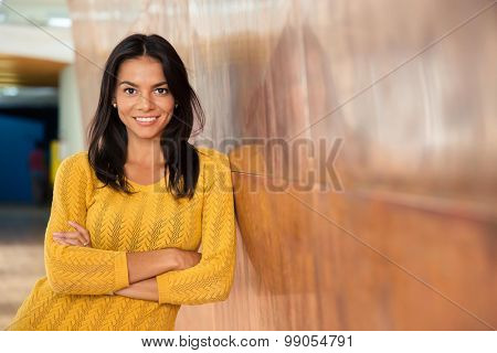 Portrait of a cheerful attractive businesswoman standing with arms folded in office