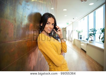 Portrait of a casual happy businesswoman talking on phone in hallway