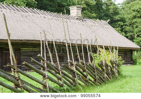 Old Wooden House With Thatched Roof And Chimney