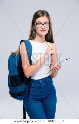 Portrait of a female teenager with backpack holding pencil and notebook isolated on a white background