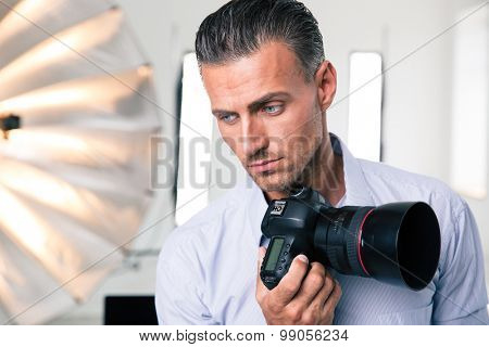 Portrait of a pensive photographer holding camera and looking at camera in studio