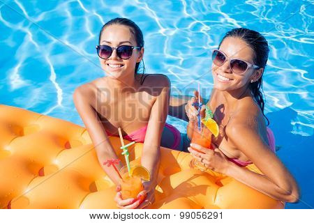 Portrait of a two smiling girlfriends drinking cocktails in swimming pool