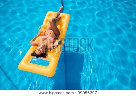 Laughing young girl lying on air mattress in the swimming pool