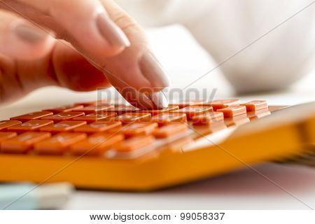 Female Accountant Or Banker Making Calculations On Orange Desk Calculator
