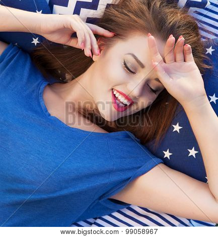 Happy beautiful young  woman with eyes closed lying in bed