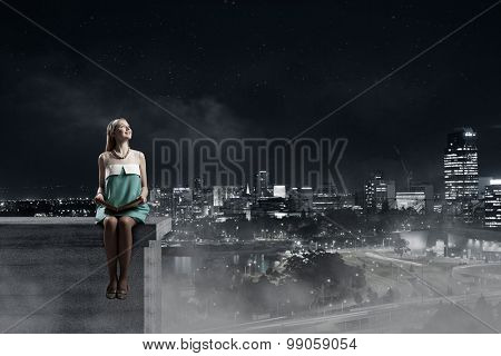 Young beautiful lady sitting on roof with book in hands