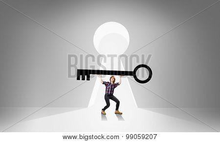 Young engineer woman lifting big key above head