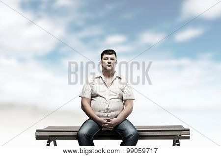 Fat man sitting on bench and looking in camera