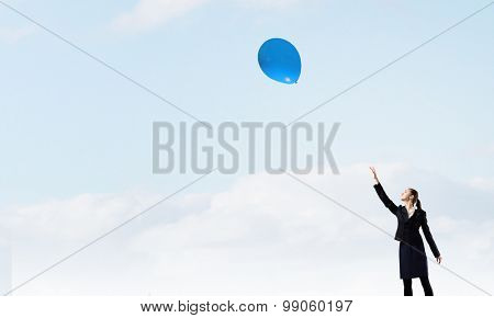 Young businesswoman reaching hand to touch balloon in sky