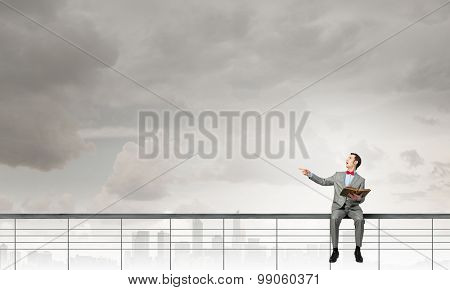 Young businessman wearing red bow tie sitting on parapet with old opened book