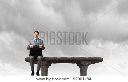 Young businessman with briefcase sitting on top of building