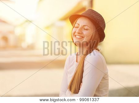 Portrait of young smiling woman in hat on the street