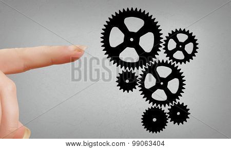 Close up of hand and gears mechanism on gray background