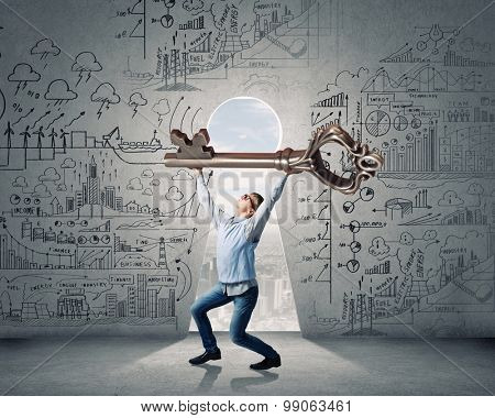 Young man in casual lifting big key above head