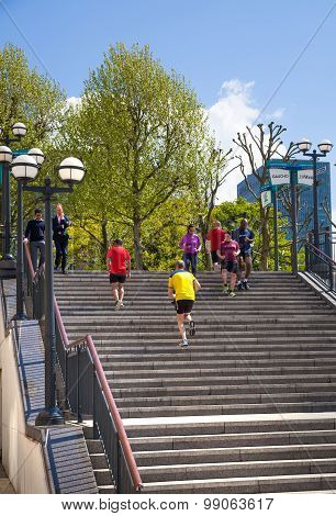Canary Wharf banking aria. Stairs up to the square with running people. Business people running duri
