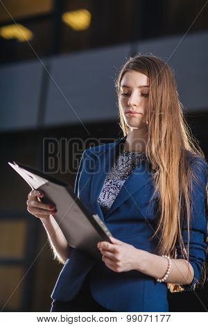 Successful Businessman Standing On Background  Buildings Looking At The Folder Charts Of Sales. City