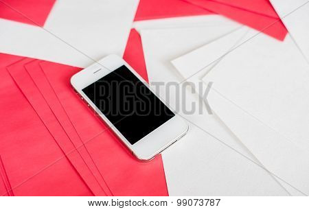 Smartphone with white and red paper sheets