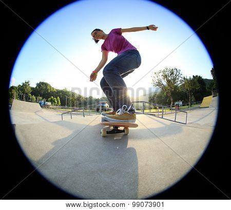 young asian woman skateboarder skateboarding at skatepark
