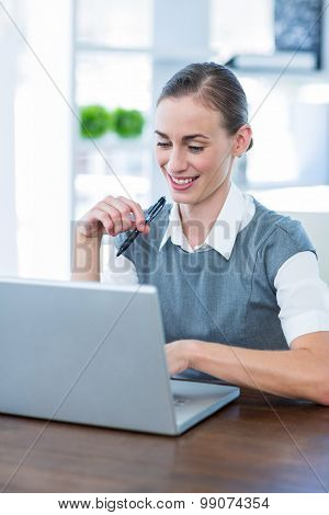 Happy businesswoman working on laptop computer in office