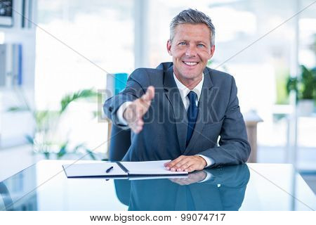 Businessman ready to shake hand in office